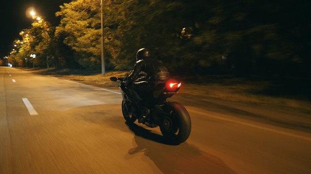 Motorcyclist racing his motorcycle on evening city. Man riding on modern sport motorbike at night street of town. Guy driving bike during trip. Concept of freedom and adventure. Rear view Close up