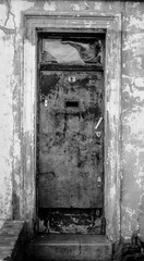 A dirty door. Black and white picture close up picture of a rough an rusty metal door.