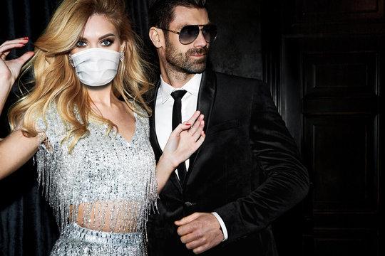 Beautiful woman in mask near the man. Sexy elegant couple.