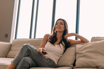 smiling woman holding remote controller and watching tv during self isolation at home
