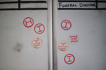Labels used to help identify clients are seen on a whiteboard in the office at Poppy's Funerals in Lambeth Cemetery, as the spread of the coronavirus disease (COVID-19) continues in London