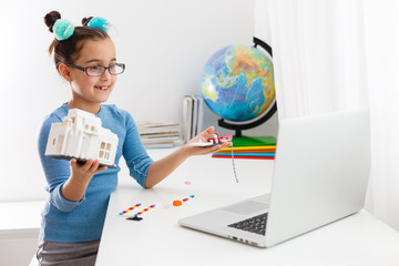 Little scientist working on new project, little girl studying robotics on laptop online
