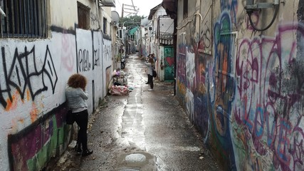 Foto auf Leinwand Graffiti People Photographing In Wet Alley Amidst Graffiti Walls