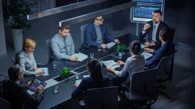 In the Corporate Meeting Room: Diverse Group of Business Associates and ExecutivesTalking, Negotiating, Debating, Working with Documents, Planning Strategy. Late at Night in the Office. High Angle