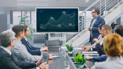In Corporate Meeting Room: Creative Director Uses Digital Interactive Whiteboard for Presentation to a Board of Executives, Investors and Businesspeople. Screen Shows Company Growth Data with Graphs