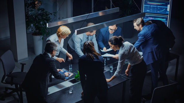 In the Dark Corporate Meeting Room Diverse Group of Executives, Business Associates and Investors Lean on a Conference Table During Emotional Discussion, Planning and Strategizing. High Angle Shot