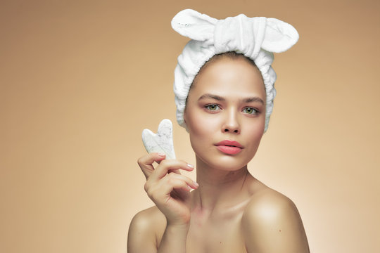 Beautiful girl with beauty gua Sha quartz stone for massage. The beige background is isolated. Cosmetic natural trend.