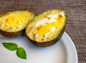 Avocado baked  eggs on white plate.