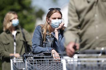 Frau mit Maske steht mit einem Einkaufswagen in einer Schlange und wartet geduldig