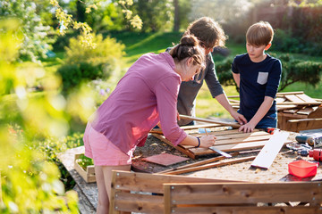 A mother and her two children build wooden planters for their permaculture vegetable garden