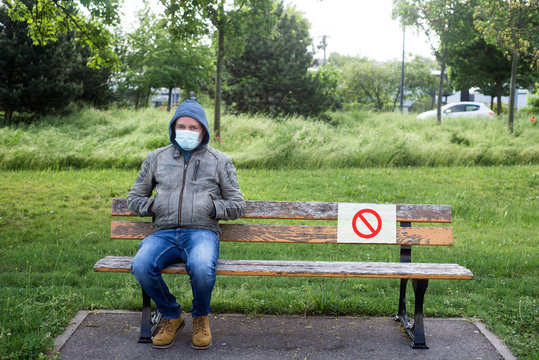 Portrait of  man sitting on wooden bench in urban park with a forbidding sign on paper - Social Distancing  concept