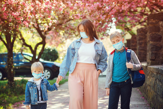 Sad family going home during quarantine. Family wearing face masks outdoors. Springtime.
