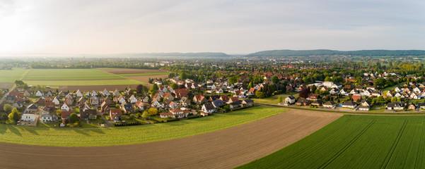 Luftaufnahme von Feldern mit einer Kleinstadt im Hintergrund Fotoväggar