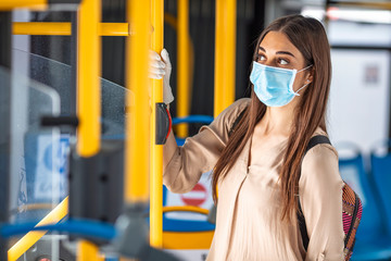 Worried Woman With Protective Face Mask In Bus Transport. Young woman wearing protective face mask, she sitting in bus transportation in the city.. Woman with mask in bus