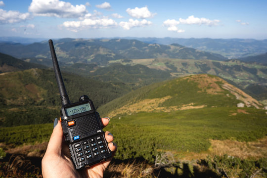 a tourist in the mountains holds a walkie-talkie to contact the group
