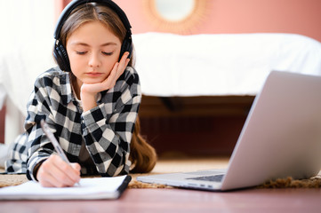 Distance home schooling. Online education. Young caucasian smart schoolgirl with headphones lies on the floor, typing in notebook, watching on laptop, smiling and doing homework.