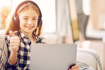 Caucasian middle schoolgirl with laptop pc and headphones at home showing thumb up and smiling. Distance education, free time, technology and internet concept