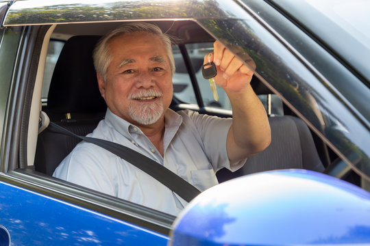 Asian senior man driver smiling and showing new car keys and sitting inside the car