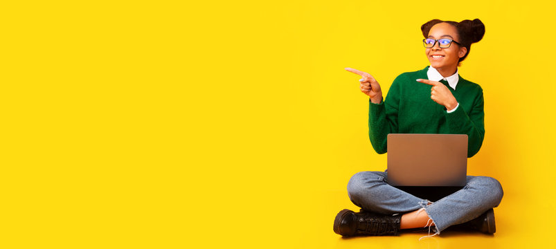 Happy afro teenager sitting on floor at studio