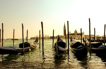 Gondolas Moored In Canal Against Clear Sky