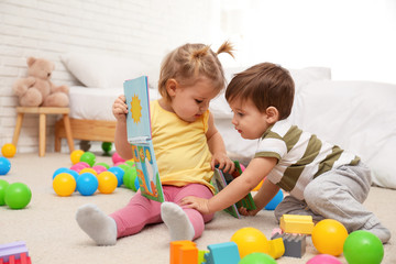 Cute little children playing with toys on floor at home