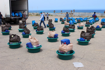 Migrants walk between food packages distributed by UNHCR in Tripoli