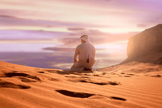 Arabic man with traditional emirates clothes sitting on kness in the UAE desert. Sunset time.