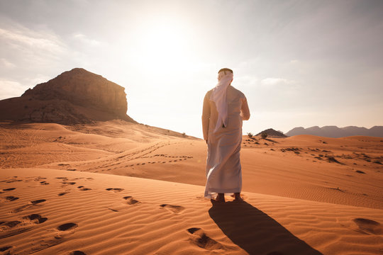 Arab man stands alone in the desert and watching the sunset.