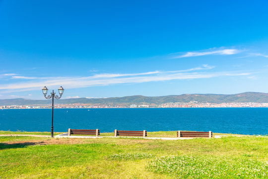 three benches on the sunny beach shore. beautiful skyline view from empty park with paved footpath on the seaside. city and mountain in the distance beneath a blue sky with clouds
