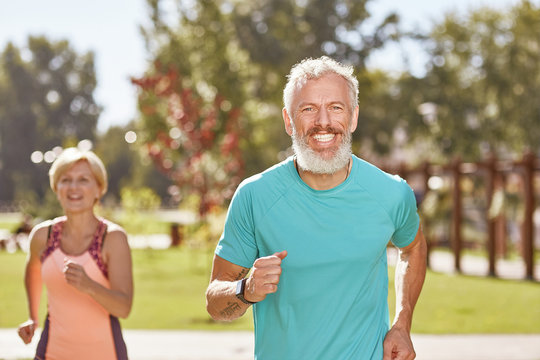 Staying healthy and fit. Happy mature man smiling at camera while running together with his wife in the early morning. Selective focus