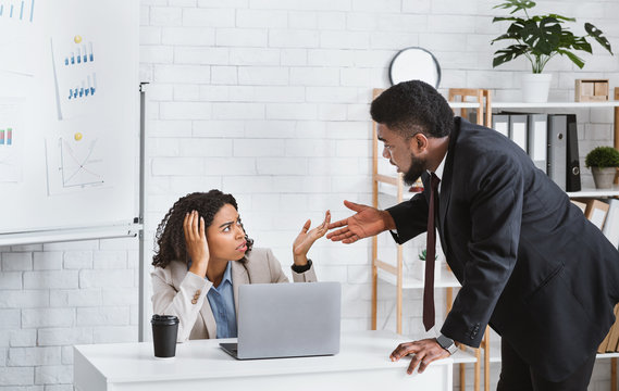 African American coworkers arguing with each other at office
