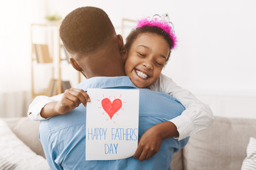 Father's day. Pretty girl giving dad postcard