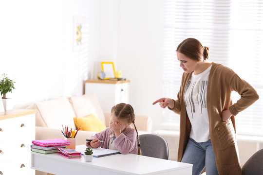 Mother scolding her daughter while helping with homework indoors