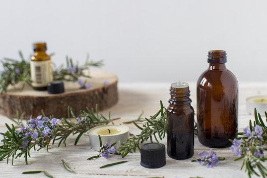 Contenitori di olio essenziale con rametti di rosmarino fioriti
