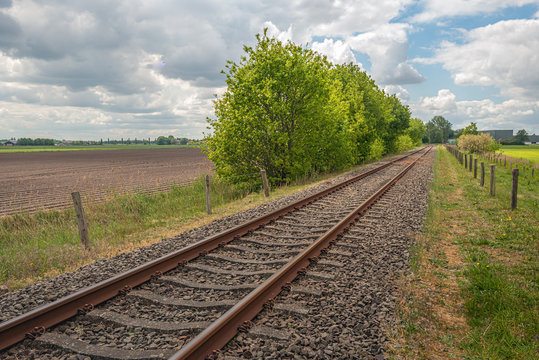 Picturesque landscape with diagonal rusty single track rails