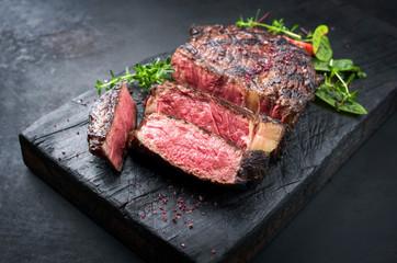 Photo sur Toile Pays d Asie Gegrilltes dry aged Wagyu Entrecote Steak vom Rind mit Salat und Salz als closeup auf einem verkohlten Holz Board