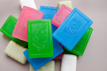 Tower of big and little multicolored soaps on beige background,top view