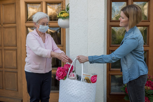 Senior woman with face mask gets shopping bag from neighborhood assistance at the house door