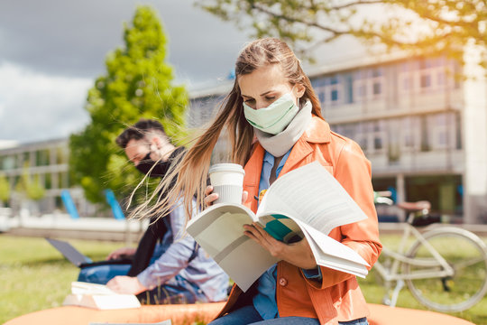 Woman student on college campus learning wearing face mask