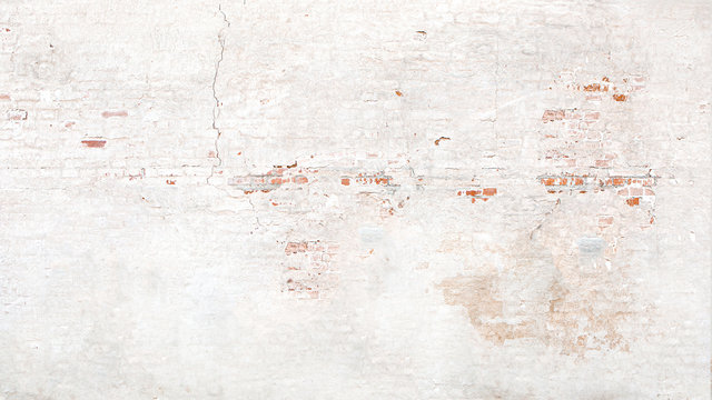 Brick wall texture with white shabby stucco, plaster. Red  and white brickwall background, white stonewall surface. Plastered wall with white uneven stucco with cracks and damages.