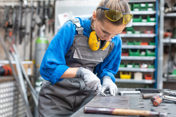 Sideview of worker woman marking piece of metal