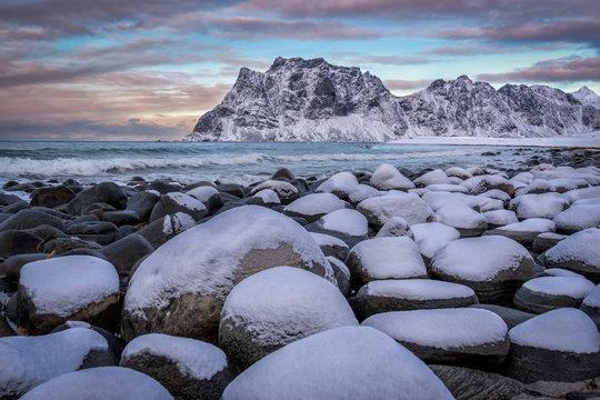 Beach with rocks covered in snow and mountains in the background in Lofoten Islands, Norway