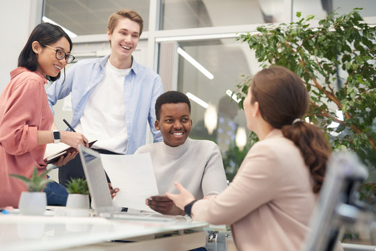 Multi-ethnic group of young business people discussing work project and smiling cheerfully during meeting in office, copy space
