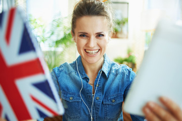 happy modern woman showing tablet PC and English flag notebook