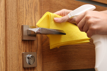 Woman cleaning door knob with rag and spray detergent, closeup
