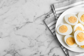 Tasty hard boiled eggs on white marble table, flat lay. Space for text