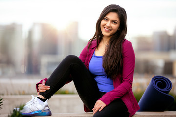 Portrait of a beautiful mixed ethnicity brunette woman in sportswear, sitting relaxed after a...