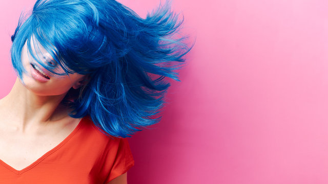 studio portrait of a sexy beautiful girl with a smile in motion on a pink background. Girl with blue hair