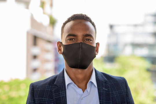 Face of young African businessman wearing mask for protection from corona virus outbreak against view of the city