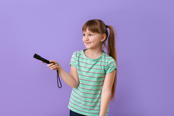 Little girl with flashlight on color background